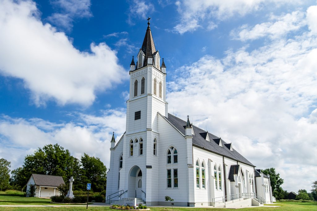 Large white church and blue sky with some clouds