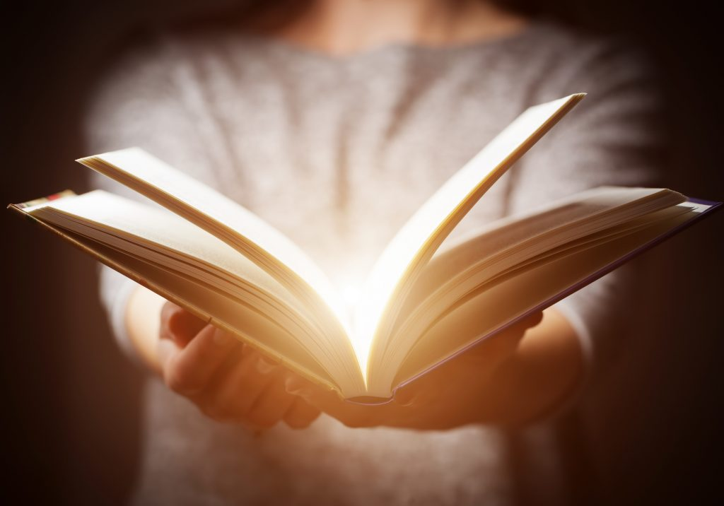 Hands holding open glowing book