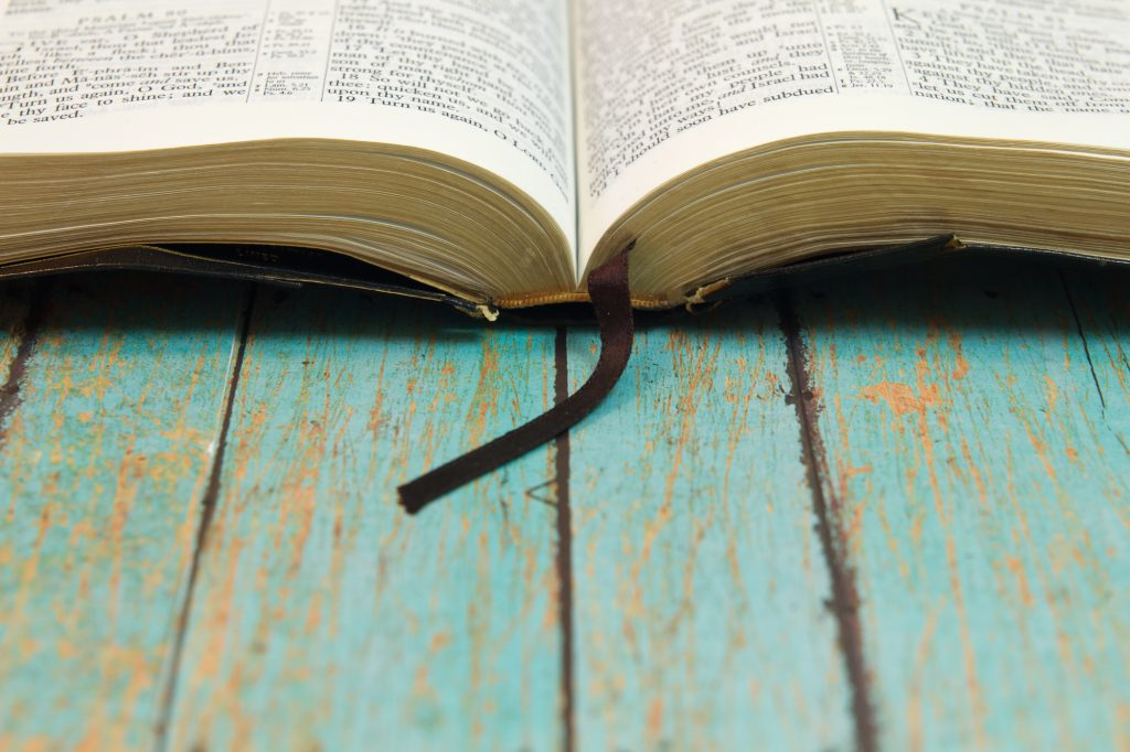 Open bible on wooden table with worn blue paint
