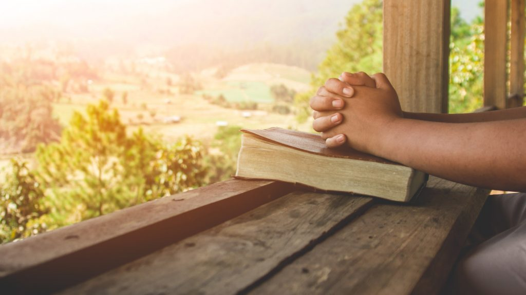 Hands praying on Bible overlooking valley