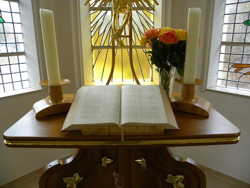 Open Bible on table with candles, flowers, and stained glass window in background